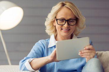 vrouwkijktoptabletmetcomputerbrilop